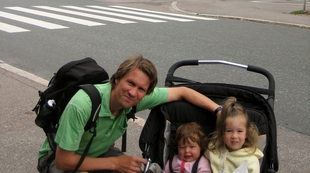 Andrew Nestingen poses next to his children in a stroller.