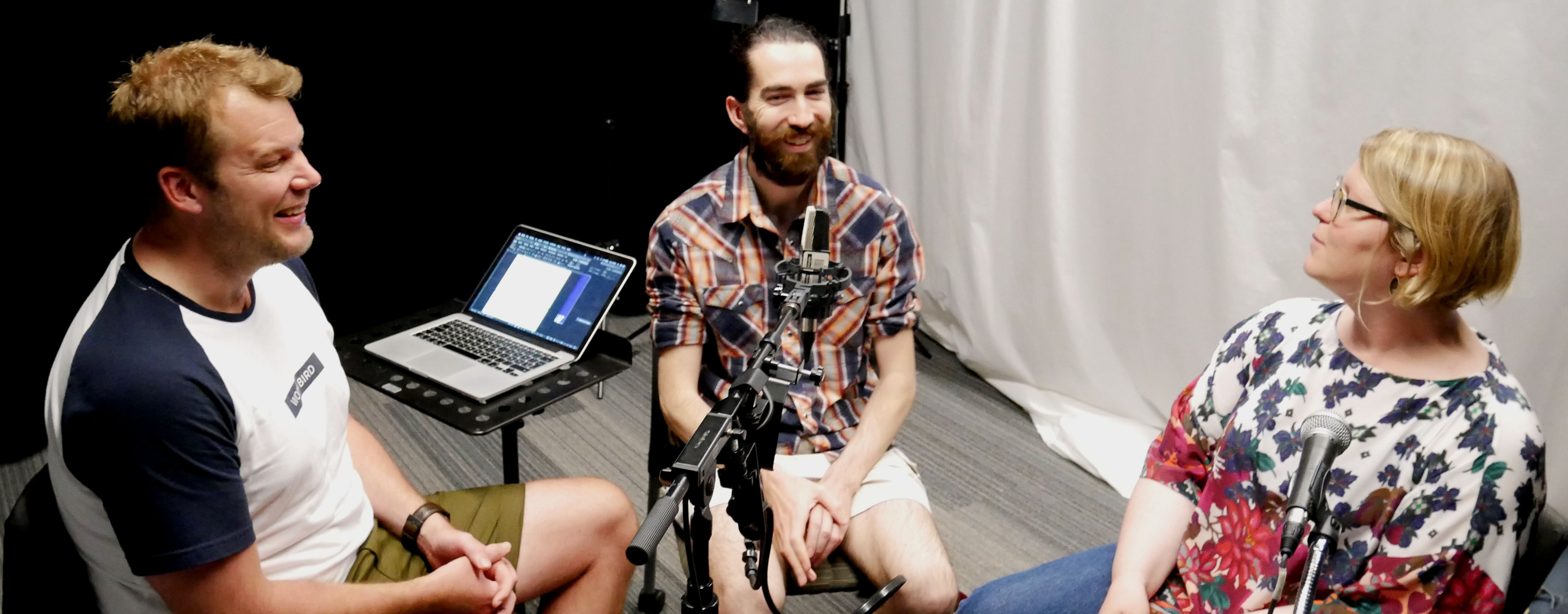 Producer Colin Connors and Kristian Naesby sit around a microphone with Olivia Gunn.