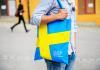 University man walking with bag, bag emblazoned with Swedish flag
